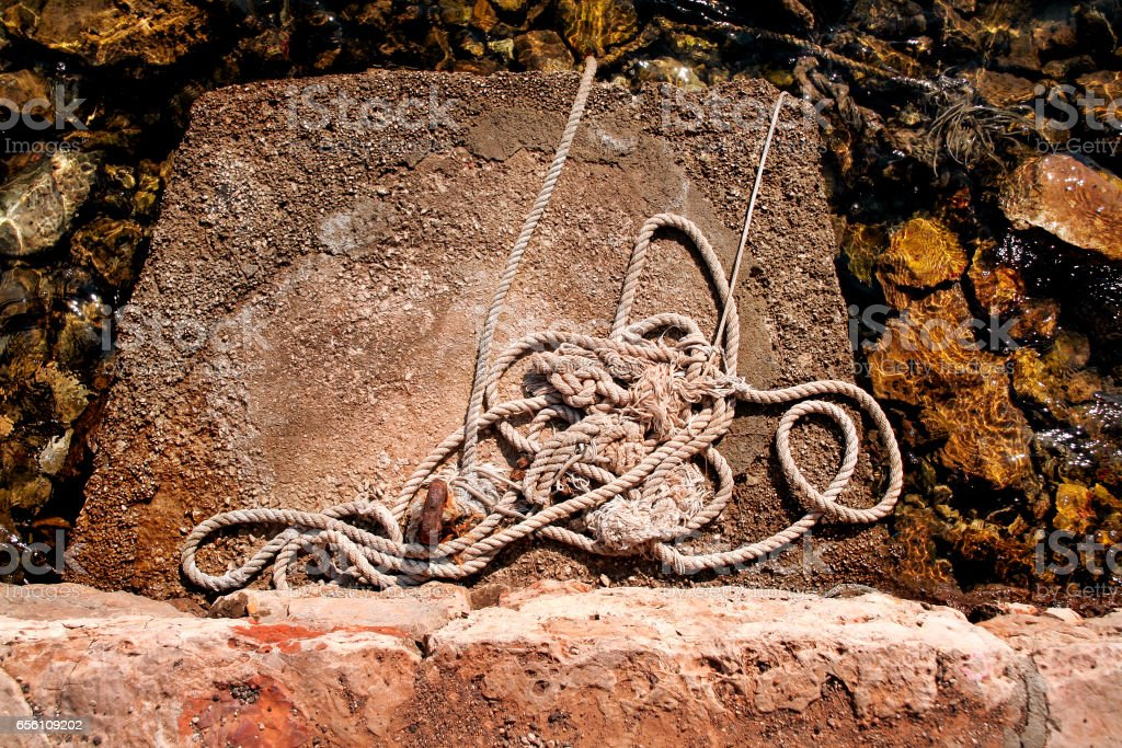 Fishing rope wrinkled and involved left on sunny rock. Cleat and rope, yacht detail. Yachting concept. Close up of boat rope tied on figure eight cleat hitch rope on the ship. stock photo
