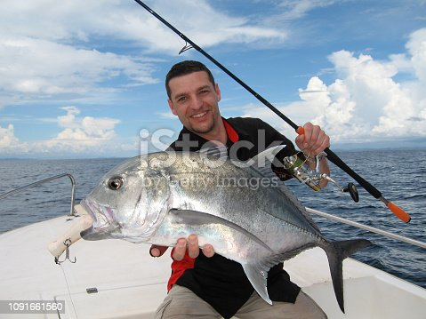 Deep sea fishing. Boat fishing, lucky fisherman holding a big trevally jack