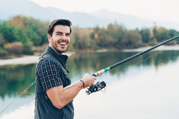 Fishing season Smiling young fisherman with fishing rod by the river fishing line stock pictures, royalty-free photos & images