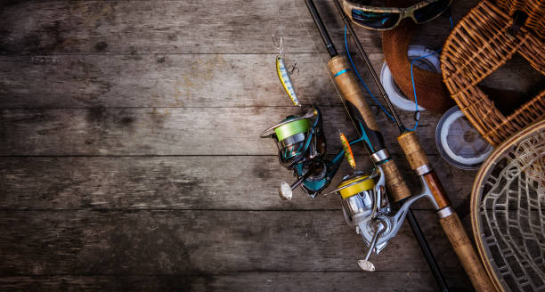 Fishing tackle background. Fishing design elements. Fishing accessories on the wooden table. Elements for advertising fishing reel stock pictures, royalty-free photos & images