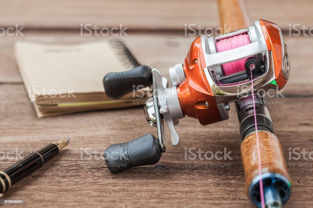 Fishing tackle - Baitcasting Reel, book on  wooden background royalty-free stock photo