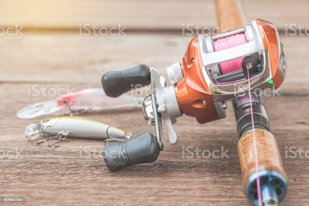 Fishing tackle - Baitcasting Reel, hooks and lures on  wooden background royalty-free stock photo