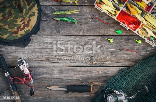 istock Fishing tackle - fishing spinning, hunting knife, hooks and lures, a fishing net and overalls. On a wooden background, top view. Copy space 951912166