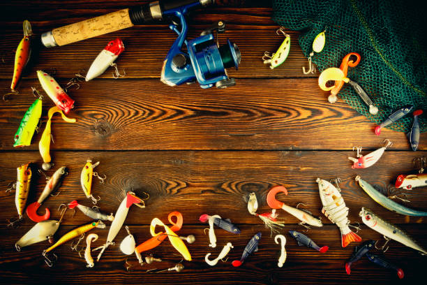 Fishing tackle spinning, still life Fishing gear, artificial bait on a predator on a wooden background, top view. fishing hook stock pictures, royalty-free photos & images