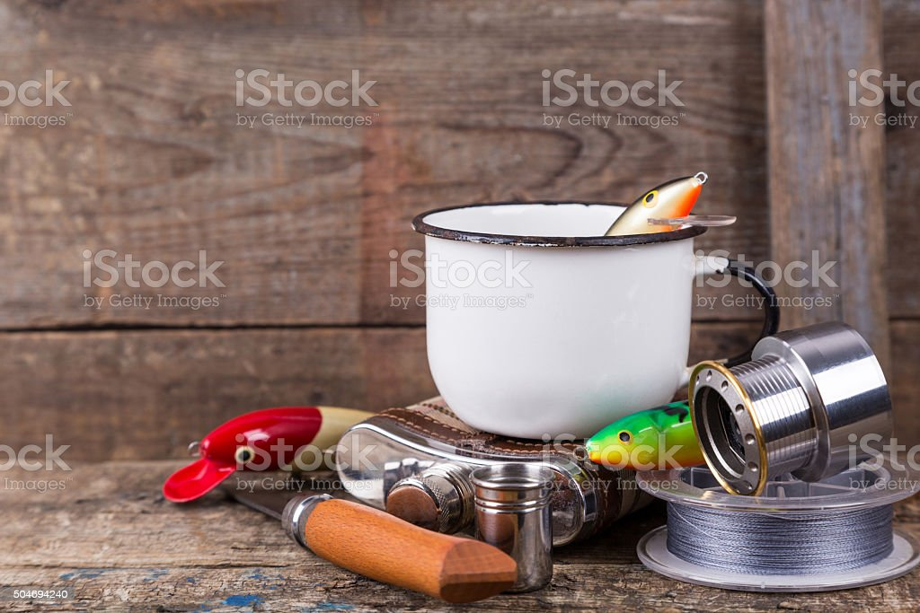 fishing tackles, baits, line with flask, knife and white cup stock photo