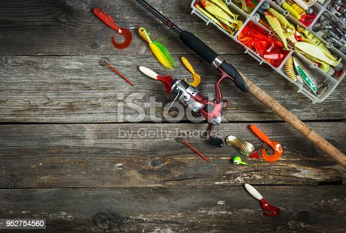 istock Fishing tackles - fishing spinning and box with color fishing tackles on wooden boards. Top view. Copy space 952754560