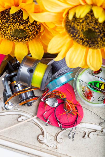 Angelausrüstungen, Leinen und Haspel mit Frühlingsdekoration mit Sonnenblumen und roten Herzen – Foto