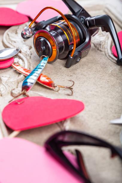 Angelausrüstungen, Linien und Haspel mit Frühlingsdekoration mit roten Herzen auf Dekorformen – Foto