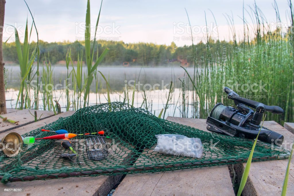 Fishing tackles on the bank of a reservoir against the background of water. stock photo