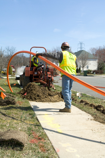 Two installers work together to install conduit for fiber optic cable.
