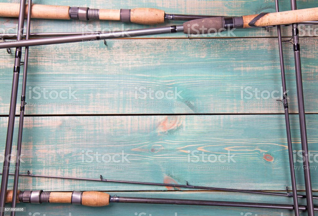 Fishing theme. Frame from fishing rods on green wooden background with free space inside. stock photo