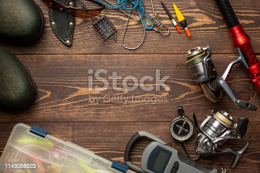 istock Fishing theme. Frame with rubber boots, fishing box, reels, fishing buoy, rod, compass, feeder, knife and fish string on wooden background. Free space 1143056523