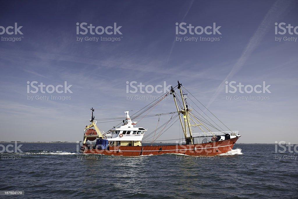 A fishing trawler cruising in the sea stock photo