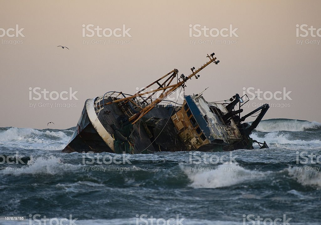 Fishing vessel boat aground on sea stock photo