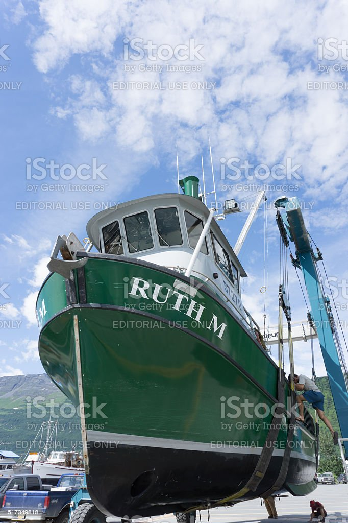 Fishing vessel sitting in boat hoist. stock photo