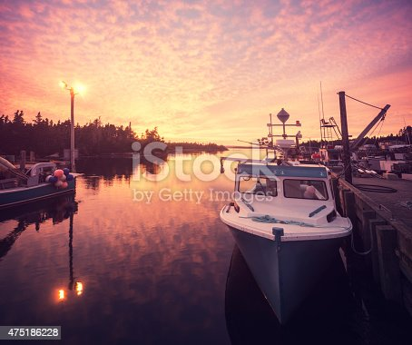 A vibrant sunset bathes a tiny fishing village in colour on Nova Scotia's Eastern Shore.