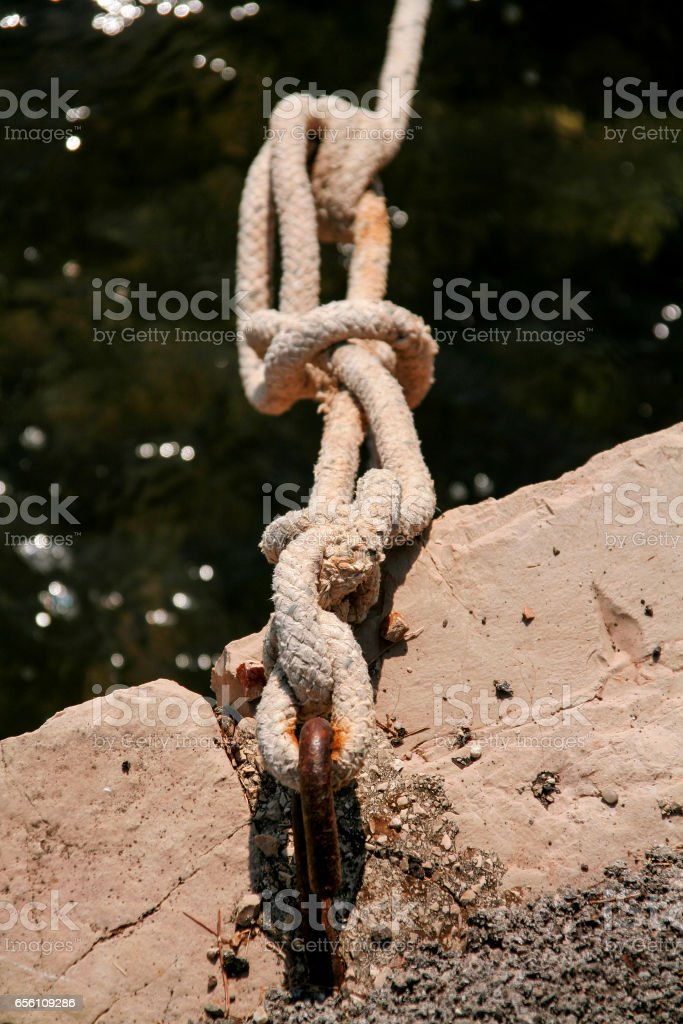 Fishing white rope tied to a hook, close-up. Cleat and rope, yacht detail. Yachting concept. Close up of boat rope tied on figure eight cleat hitch rope on the ship. stock photo