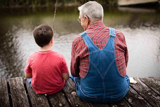 Fishing With Grandpa, Rear View Color image of a young boy fishing with his grandfather while sitting on a dock. bib overalls boy stock pictures, royalty-free photos & images