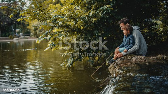 Little smiling boy is learning how to catch a fish in a park pond, with a little help of his father; wide photo dimensions