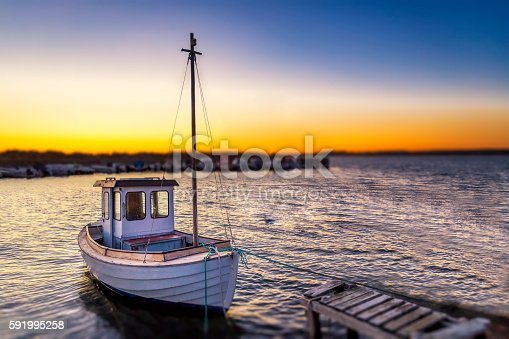 Fishingboat  tied up by a small jetty in tranquil water during a sunset evening