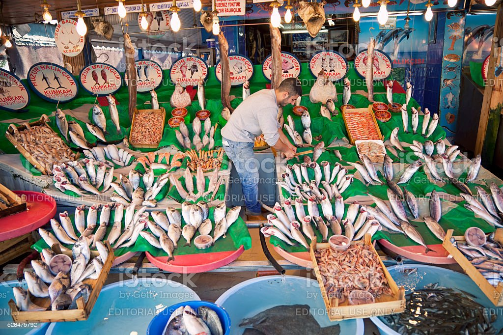 Fishmonger arranging fishes on table stock photo