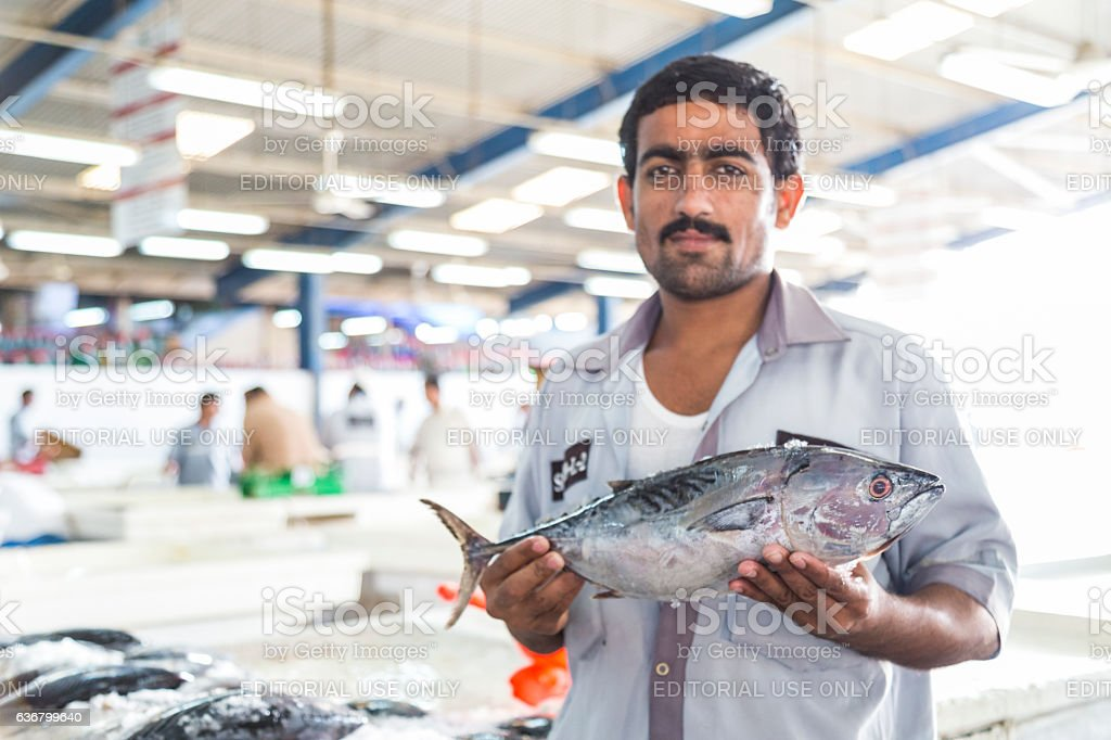 Fishmonger showing his fish of the day. stock photo