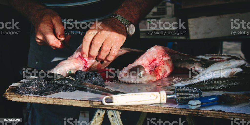 Fishmonger skinning dogfish (Mazzola) at a Mediterranean fish market stock photo