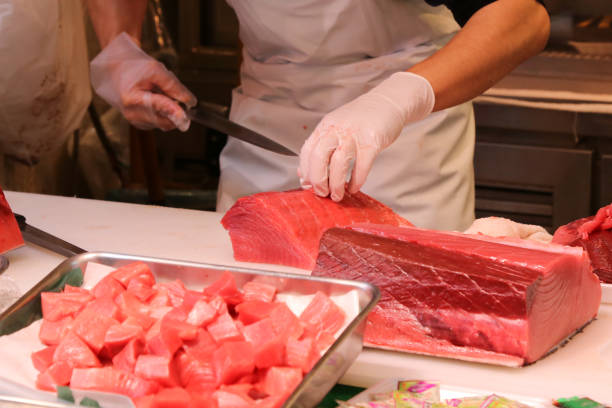 Fishmonger use knife to slice the big tuna fish to a piece at the fish market in Japan. stock photo