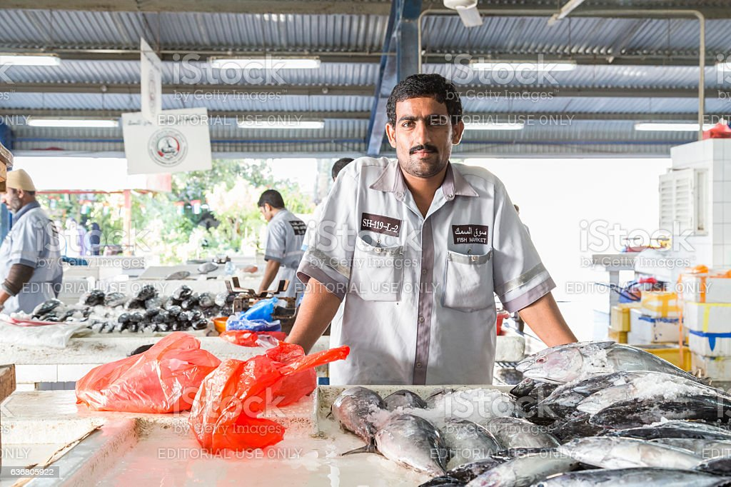Fishmonger waiting patiently at his table for customers. stock photo