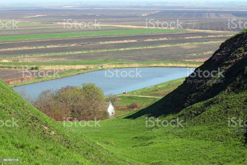 fishpond and green hills country landscape stock photo