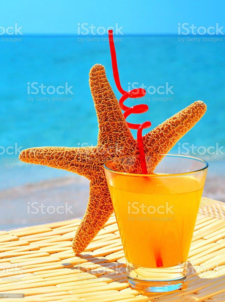 Fishstar, glass of orange cocktail against the blue sea stock photo