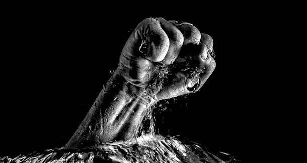 Fist breaking trough water stock photo