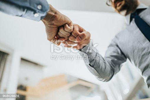 Close up of two unrecognizable businessmen greeting each other with fist bump.