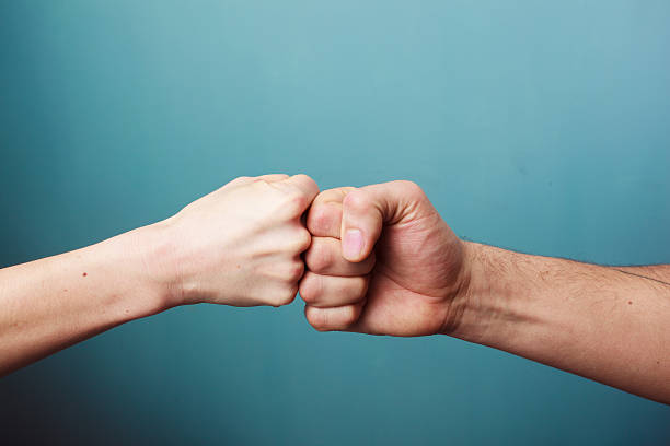fist bump - knuckle stock photos and pictures
