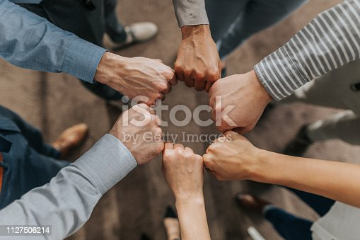 Above view of unrecognizable business team making a circle with their fists.