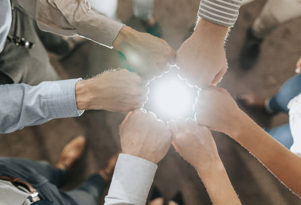 Fist bump unity! Above view of unrecognizable business team making a circle around lens flare with their fists. dignity stock pictures, royalty-free photos & images