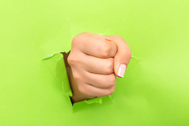 Fist coming out the paper hole isolated on green background – Foto