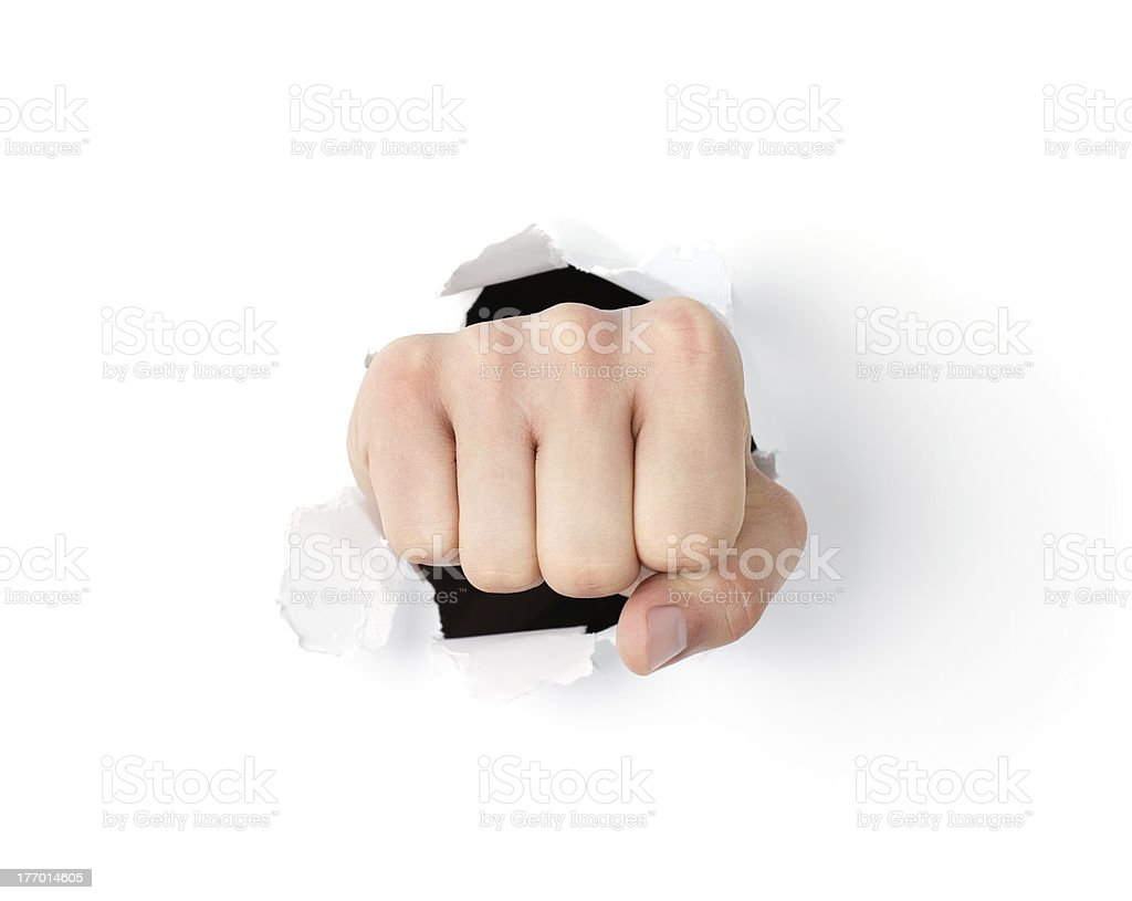 Fist coming out the paper hole royalty-free stock photo