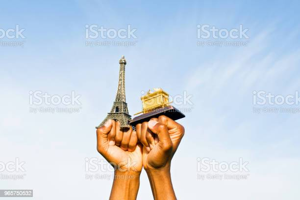 Fist Hold Up The Eiffel Tower And Ark Of The Covenant Replica Stock Photo - Download Image Now