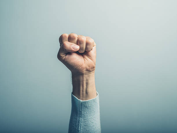 fist in the air - courage stock photos and pictures