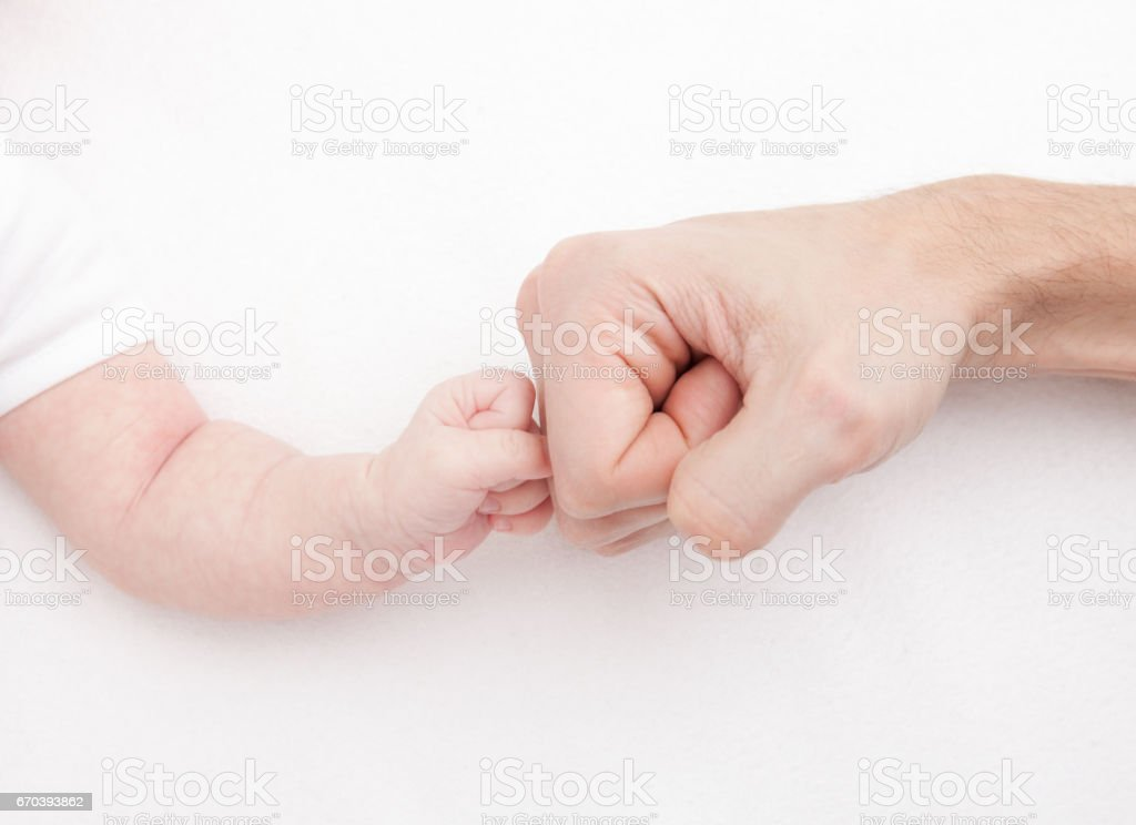 Fist of Dad and Newborn Baby. Fist to fist stock photo