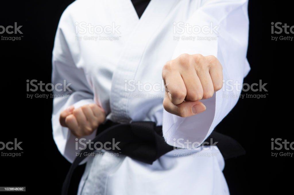 Fist of woman wearing Karate uniform in front of black background