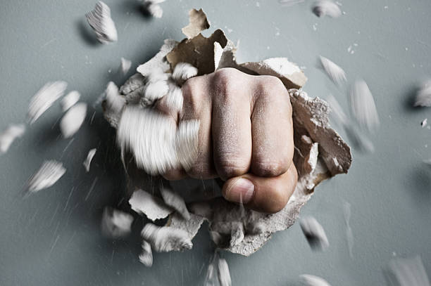 fist a wall is broken through by a fist demolishing stock pictures, royalty-free photos & images