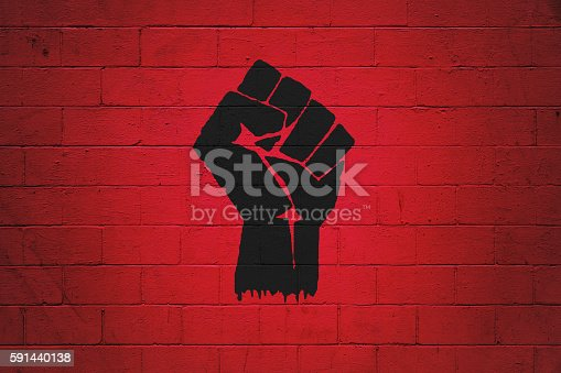 Black fist painted on a red brick wall. Ideal to serve as wallpaper or the base for a bigger composition.