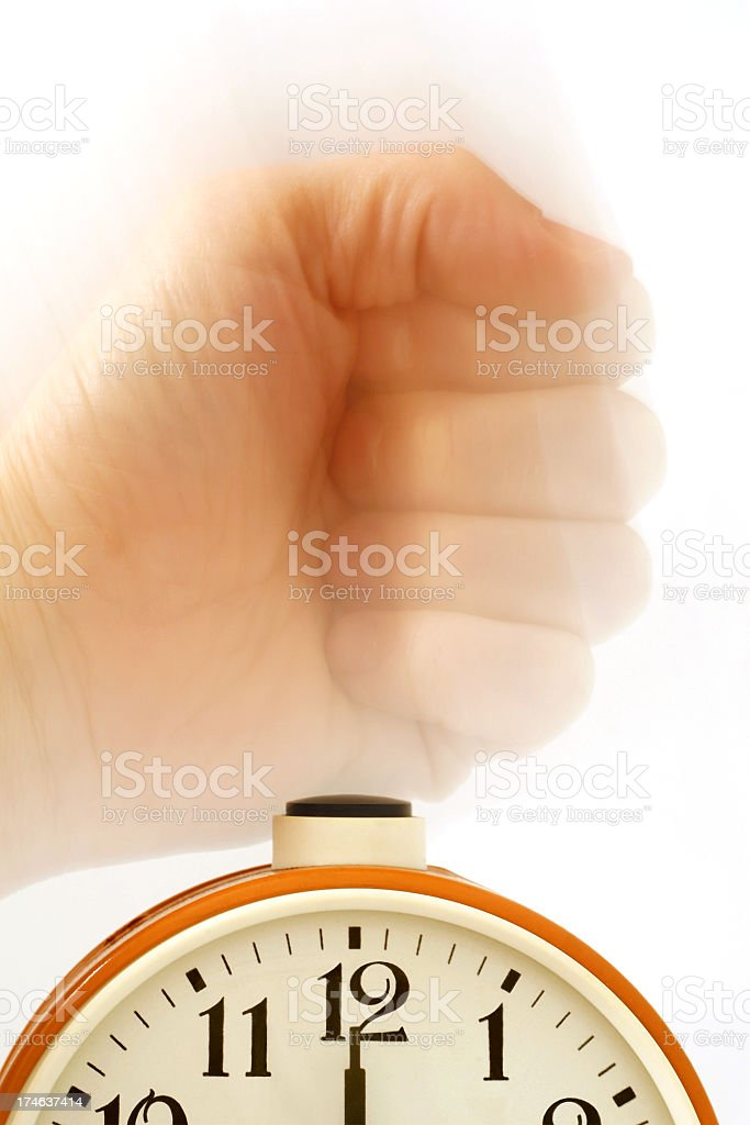 Fist punching alarm clock in the morning royalty-free stock photo