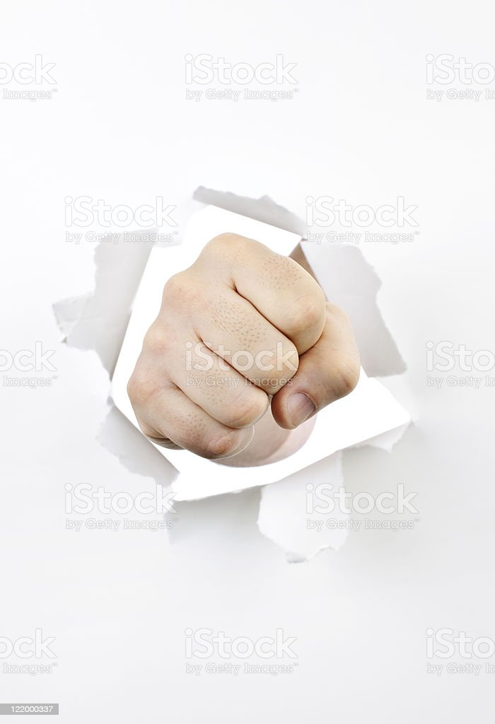 Fist punching through hole in paper stock photo