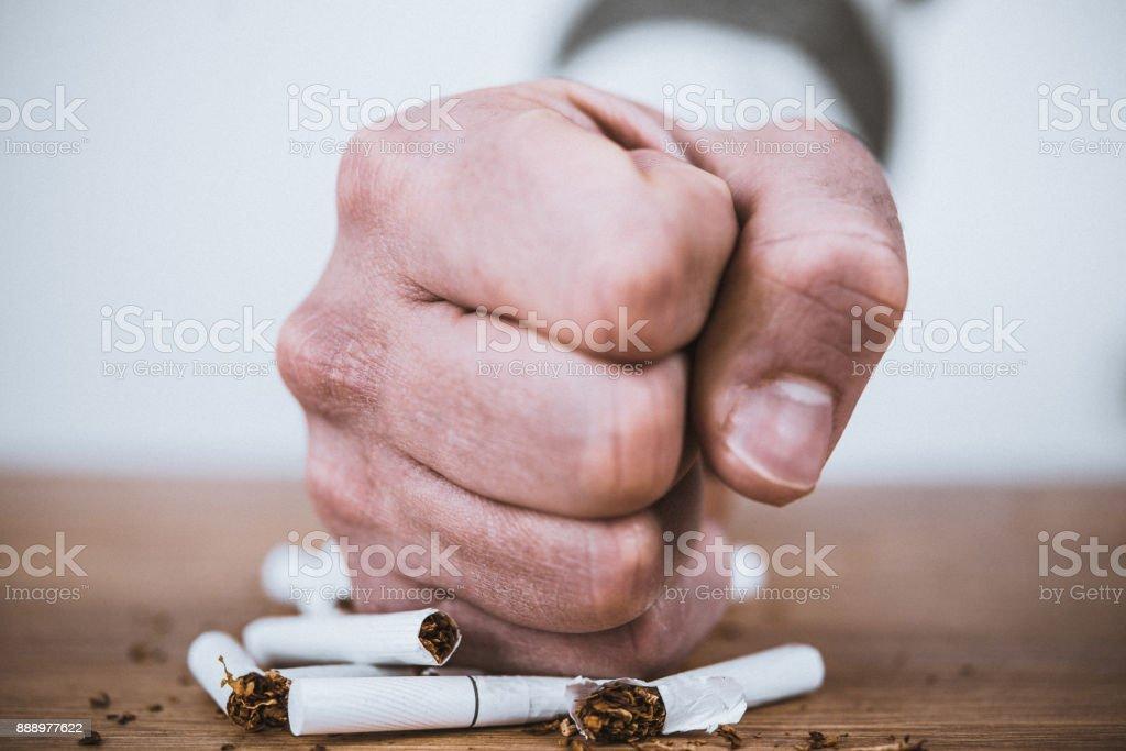 Fist smashing cigarettes stock photo