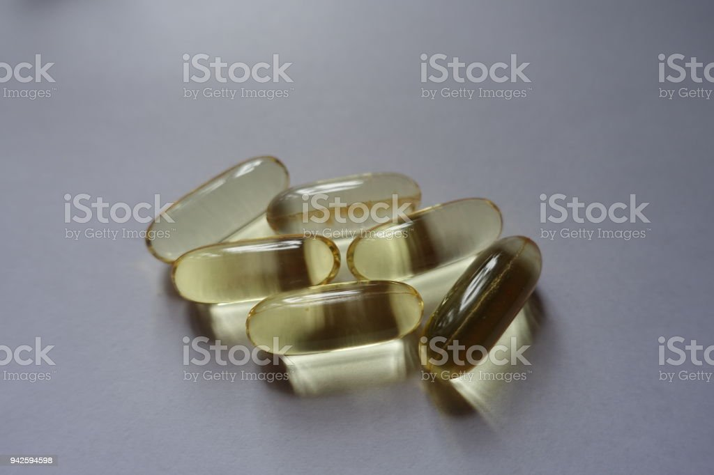 Fistful of softgel capsules of fish oil stock photo