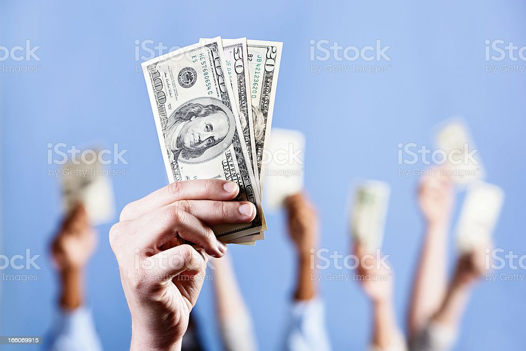 Fistful of US dollars; many more in background stock photo