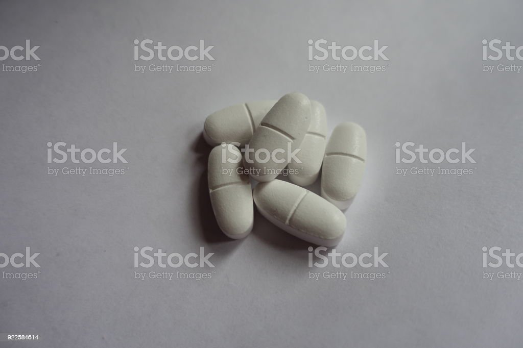 Fistful of white oblong caplets of calcium citrate stock photo